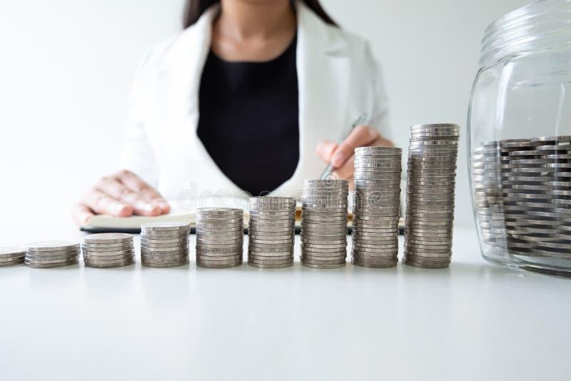 Vrouwenhand het schrijven de muntstukken in flessenbank met muntstukkengrafiek voeren groeiende zaken aan succes en het sparen vo royalty-vrije stock afbeelding