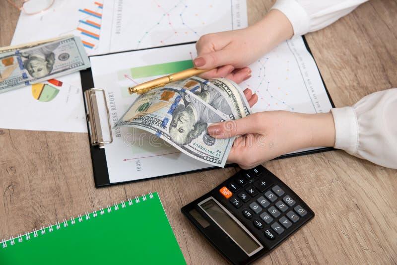 Vrouwenhand met calculator en bedrijfsdiagram stock afbeelding