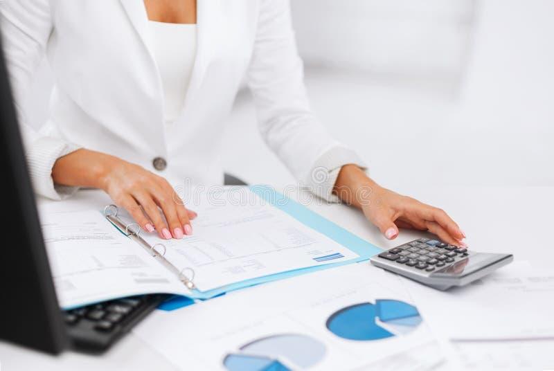 Vrouwenhand met calculator en documenten stock fotografie