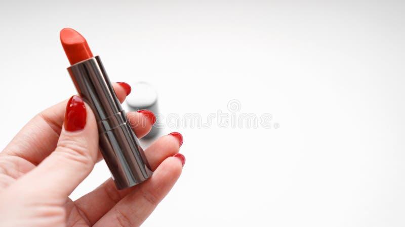 Vrouwenhand met de Rode Rode Lippenstift van de Spijkersholding Sluit omhoog van vrouwelijke hand royalty-vrije stock foto