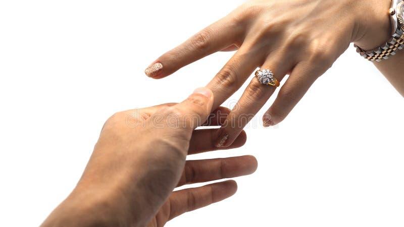 Vrouwenhand met gouden diamantring en een kerelhand die haar wijsvinger houden royalty-vrije stock fotografie