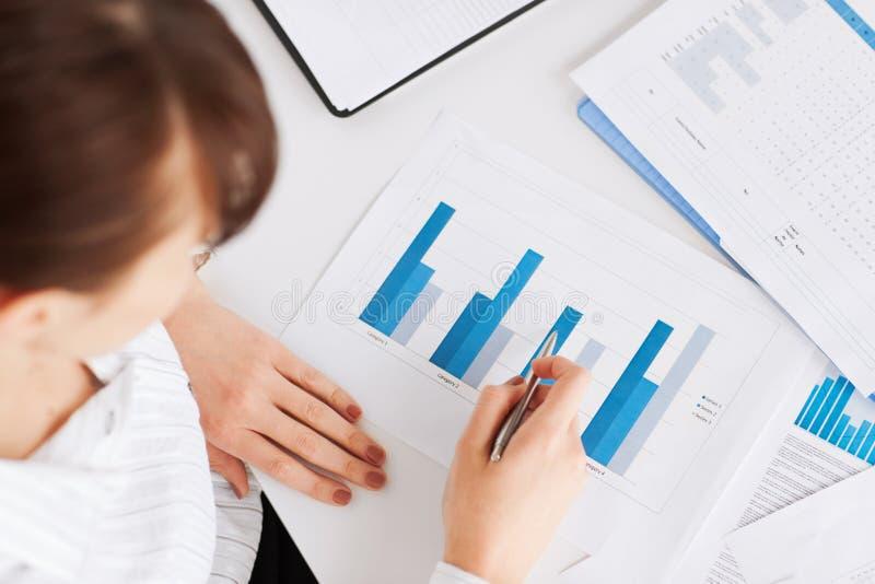 Vrouwenhand met grafieken en documenten stock afbeeldingen