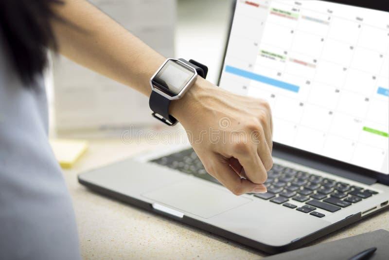 Vrouwenhand met slim horloge op pols Planningsagenda en programma die de ontwerper van de kalendergebeurtenis gebruiken De kalend royalty-vrije stock foto