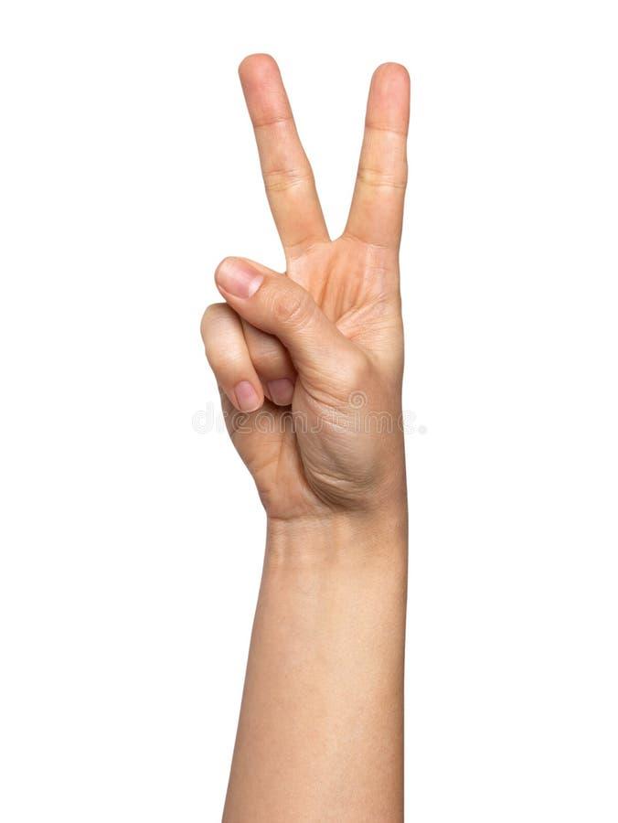 Vrouwenhand met twee die vingersconcept overwinning op witte achtergrond wordt geïsoleerd stock afbeelding