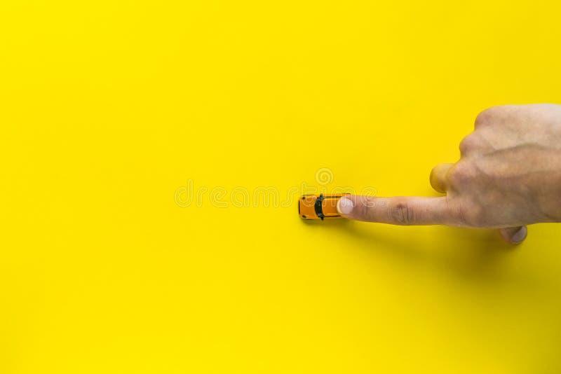 Vrouwenhand met Weinig Gele stuk speelgoed auto op een gele achtergrond Vrije ruimte voor tekst Concept royalty-vrije stock foto's