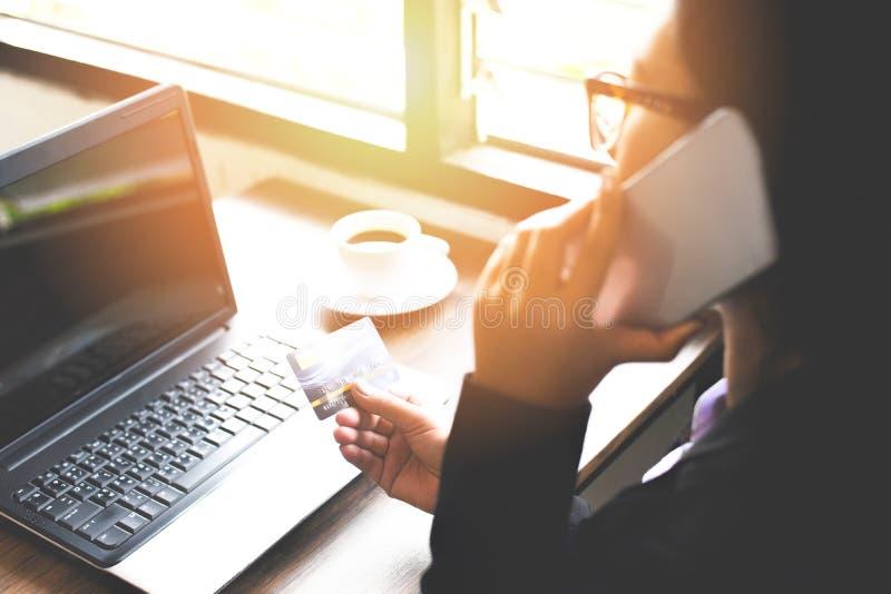 Vrouwenhanden creditcard houden en laptop met behulp van en mobiele telefoon die voor online het winkelen in het boodschappenwage stock foto's