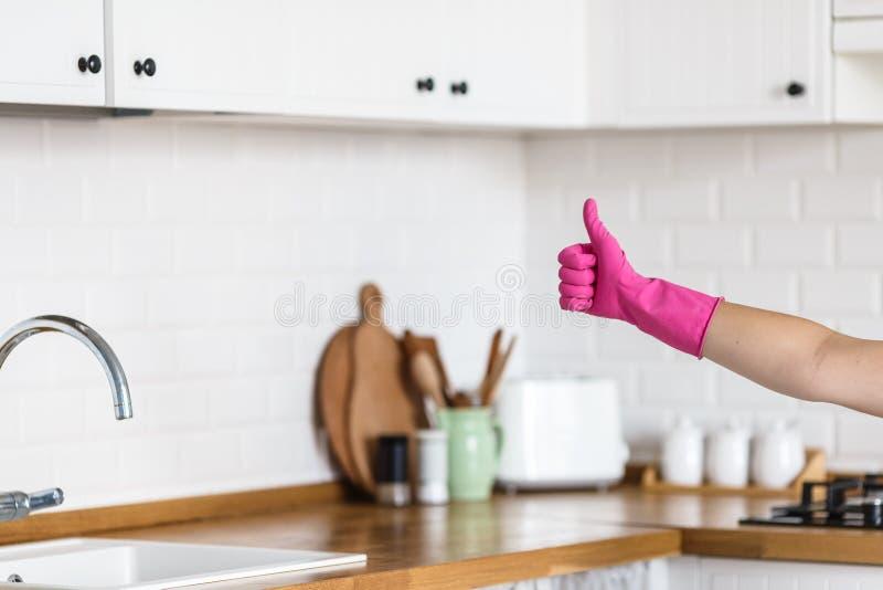 Vrouwenhanden die beschermende handschoenen op witte keukenachtergrond dragen Concept schone keuken, succesvolle duim omhoog ja o stock afbeelding