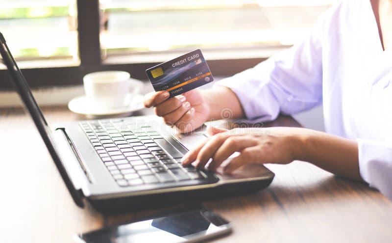 Vrouwenhanden die creditcard houden en laptop voor online het winkelen op een achtergrond van de de koffiekop van de bureaulijst/ royalty-vrije stock afbeelding