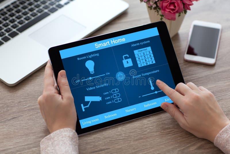 Vrouwenhanden die de computer slim huis houden van tabletpc dichtbij laptop royalty-vrije stock foto's