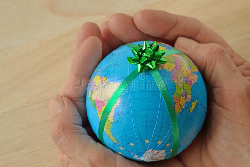 Vrouwenhanden die de Wereld met een groen lint houden - Concept het beschermen en de wereld bewaren; concept de wereld als gift stock afbeelding
