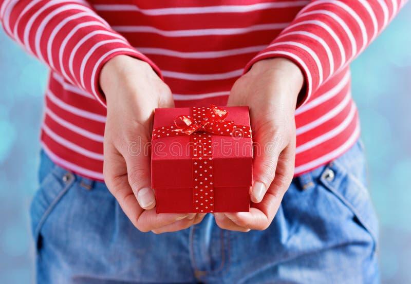 Vrouwenhanden die een gift of een huidige doos met boog van rood lint houden voor Valentijnskaartendag stock afbeeldingen