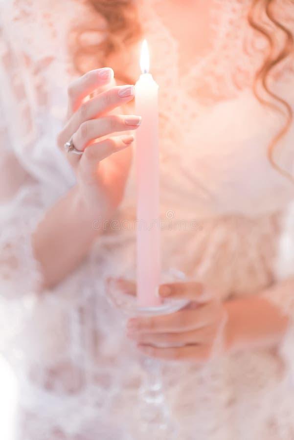 Vrouwenhanden die een kaars in een kanten witte kleding houden stock afbeeldingen