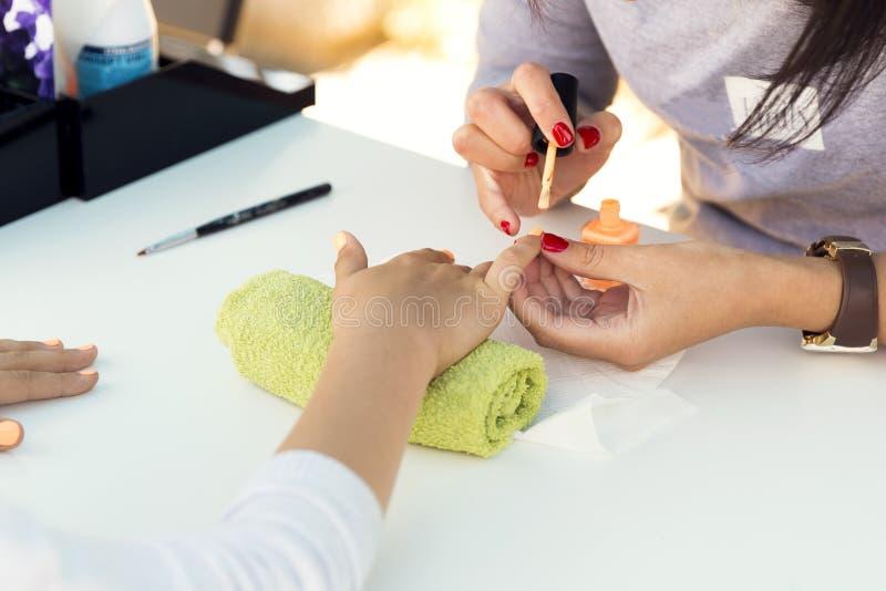 Vrouwenhanden die een manicure in schoonheidssalon ontvangen, in openlucht schoonheidsfestival Spijker het indienen stock fotografie