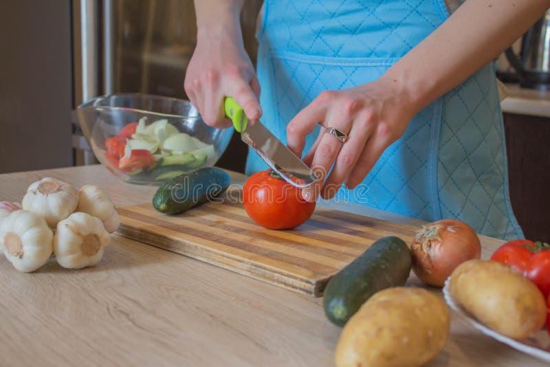 Vrouwenhanden die gezonde maaltijd in de keuken, achter verse groenten koken Bebouwd beeld van jonge meisjes scherpe groenten voo stock foto's