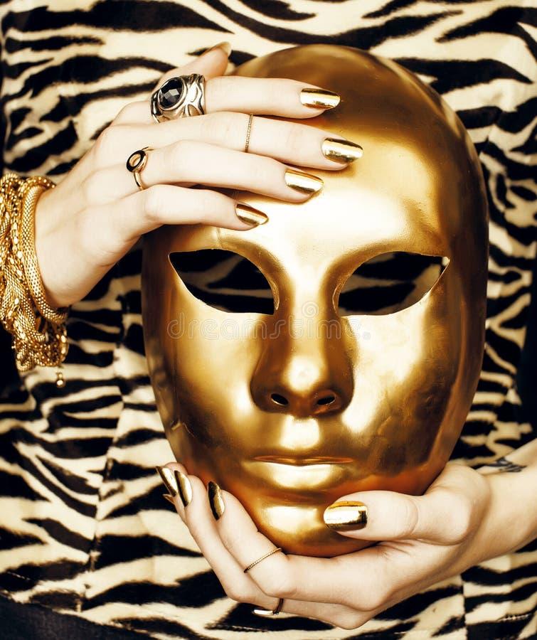 Vrouwenhanden die gouden Carnaval-masker, rijke luxemanicure en juwelen dicht op gestreepte druk tegenhouden stock afbeeldingen