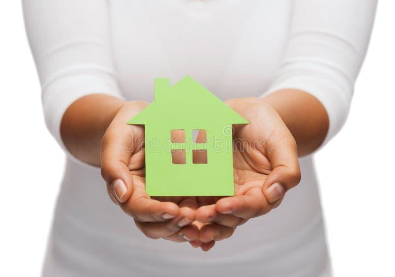 Vrouwenhanden die groen huis houden stock foto