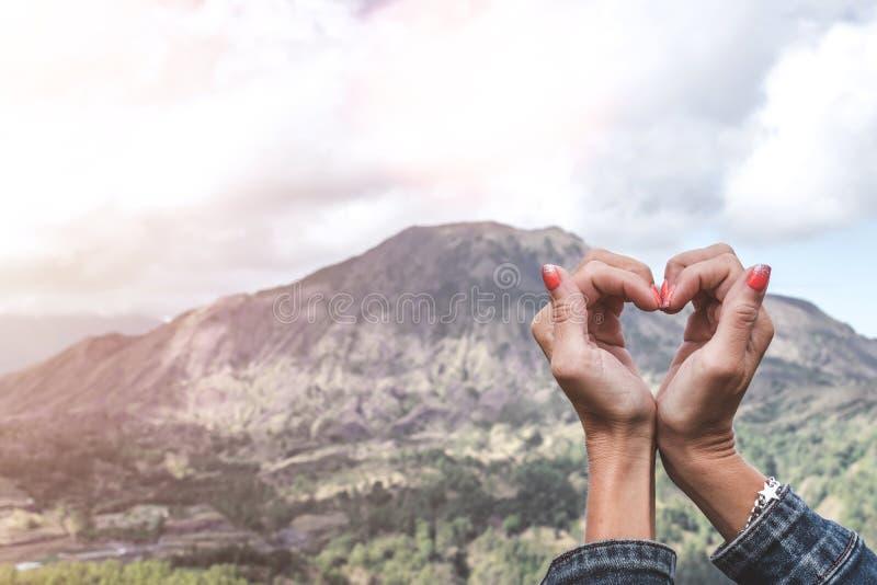 Vrouwenhanden die hart op een mooie achtergrond van Batur van de bergvulkaan maken Het eiland van Bali zonlicht indonesië royalty-vrije stock foto's