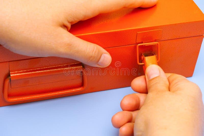 Vrouwenhanden die het slot op oranje metaaldoos openen stock foto