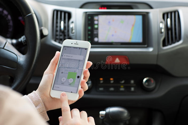 Vrouwenhanden die iPhone 6S met toepassingstaxi Uber houden royalty-vrije stock foto's