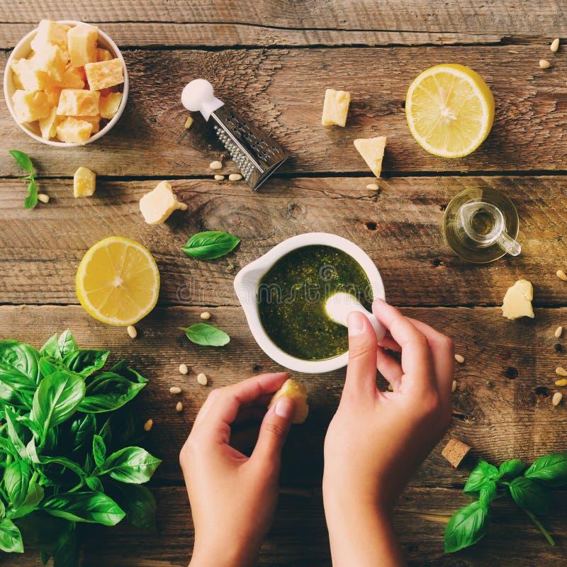 Vrouwenhanden die Italiaanse pesto in kom maken Ingrediënten - basilicum, citroen, parmezaanse kaas, pijnboomnoten, knoflook, oli royalty-vrije stock afbeeldingen