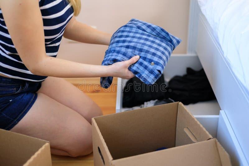 Vrouwenhanden die kleren zetten om doos te schenken stock foto's