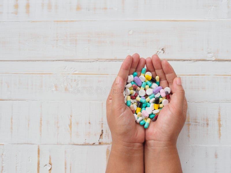 Vrouwenhanden die kleurrijke pillen op witte houten achtergrond houden H royalty-vrije stock foto's