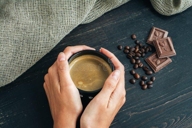 Vrouwenhanden die mok die hete koffie houden, zich op houten lijst met chocolade, koffiebonen en jute bevinden royalty-vrije stock foto