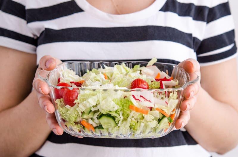 Vrouwenhanden die veganist plantaardige salade houden stock fotografie