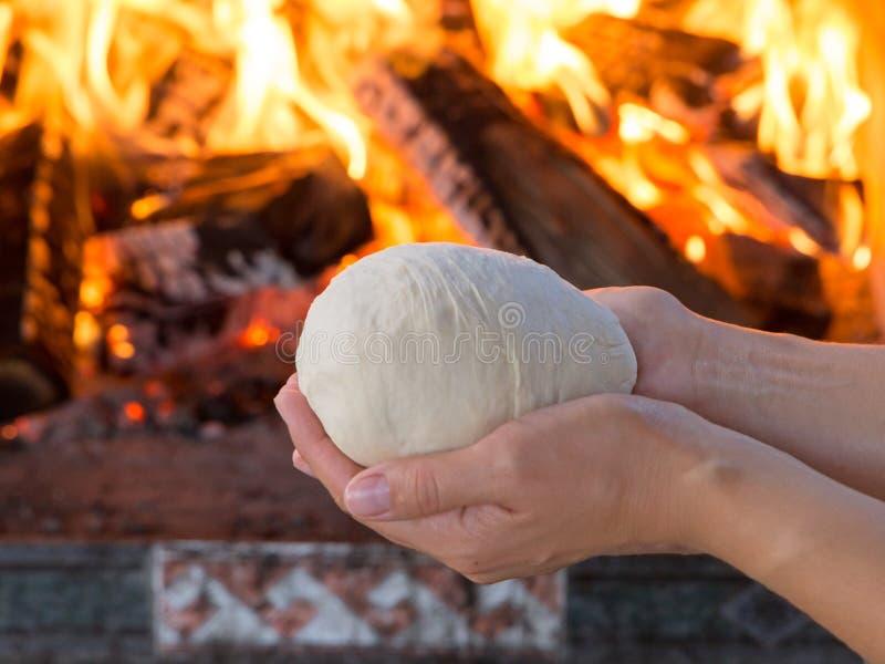 Vrouwenhanden die vers ruw deeg voor pizza of broodbaksel op houten lijst maken tegen de Brandende open haard comfortstemming royalty-vrije stock afbeeldingen