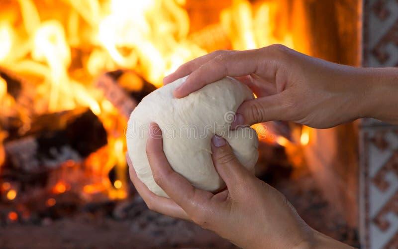 Vrouwenhanden die vers ruw deeg voor pizza of broodbaksel op houten lijst maken tegen de Brandende open haard comfortstemming royalty-vrije stock foto