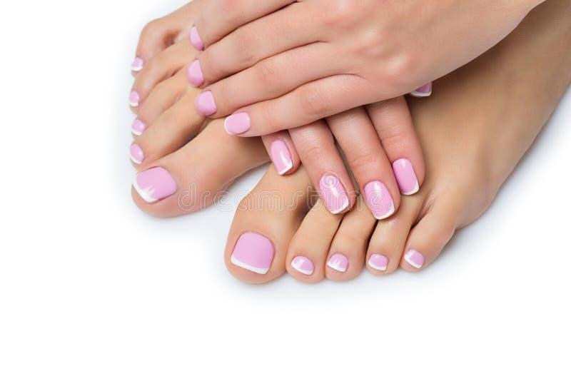 Vrouwenhanden en voeten met Franse manicure royalty-vrije stock fotografie