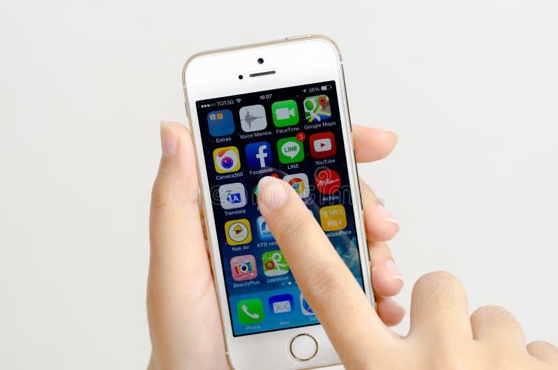 Vrouwenhanden het houden en wat betreft een Apple-iPhone 5s royalty-vrije stock foto