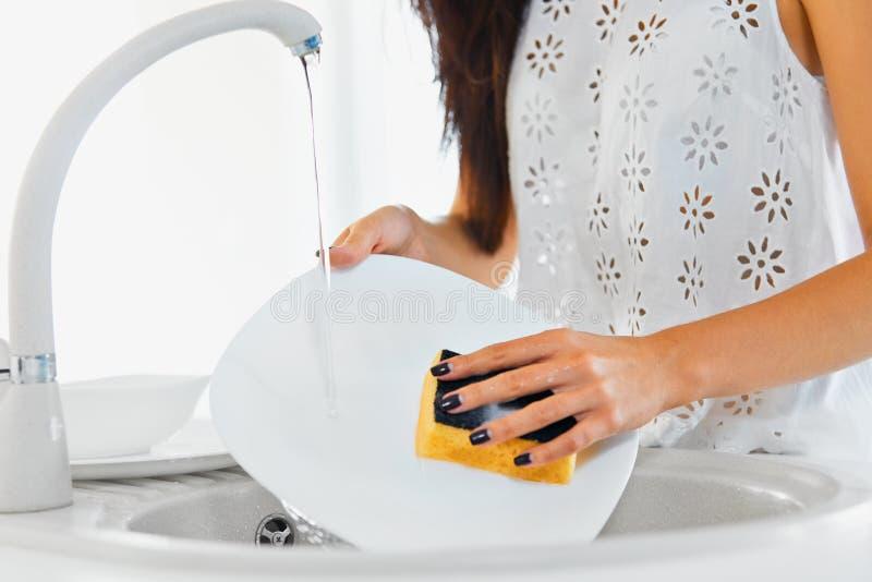 Vrouwenhanden met de aardige schotels van de manicurewas in de keuken royalty-vrije stock afbeeldingen