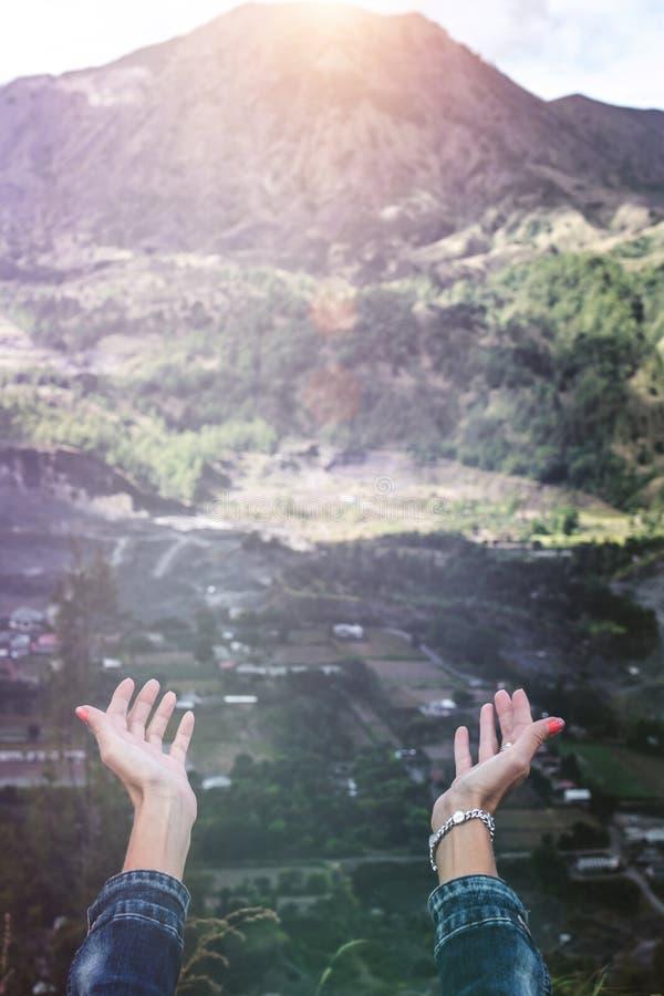 Vrouwenhanden op bergachtergrond Vulkaan Batur Het eiland van Bali stock foto's