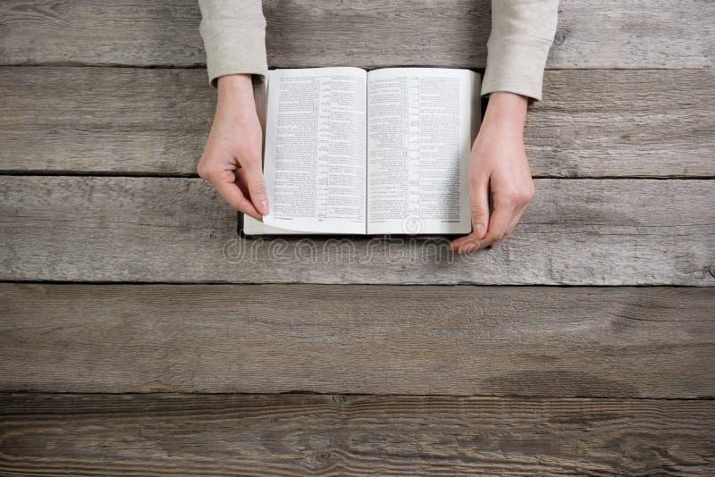 Vrouwenhanden op bijbel zij leest en bidt stock afbeelding