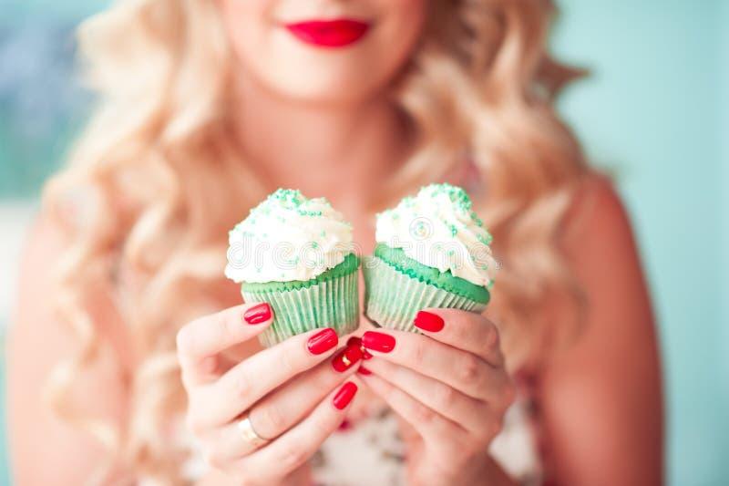 Vrouwenholding cupcakes royalty-vrije stock fotografie