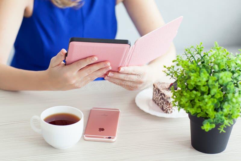 Vrouwenholding in de hand eReader Kindle Paperwhite royalty-vrije stock foto