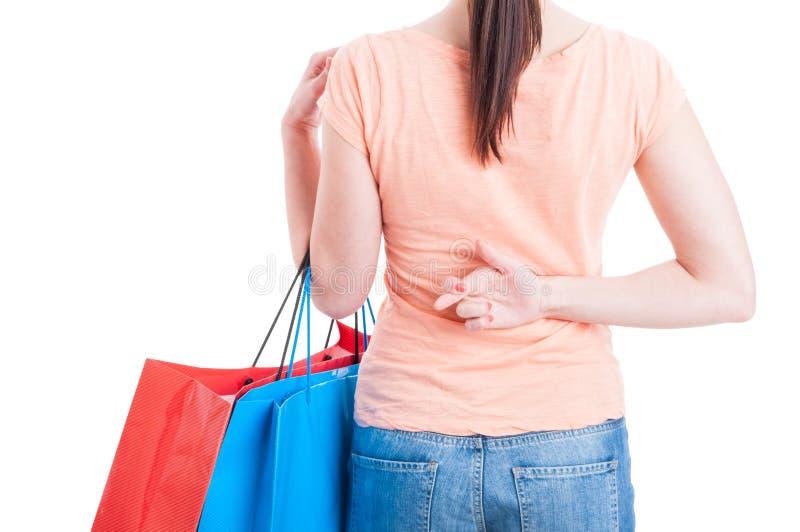 Vrouwenholding het winkelen zakken die die vingers tonen achter rug worden gekruist stock afbeelding