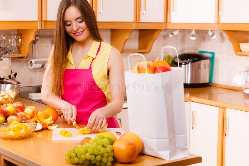 Vrouwenhuisvrouw in keuken scherpe oranje vruchten royalty-vrije stock fotografie