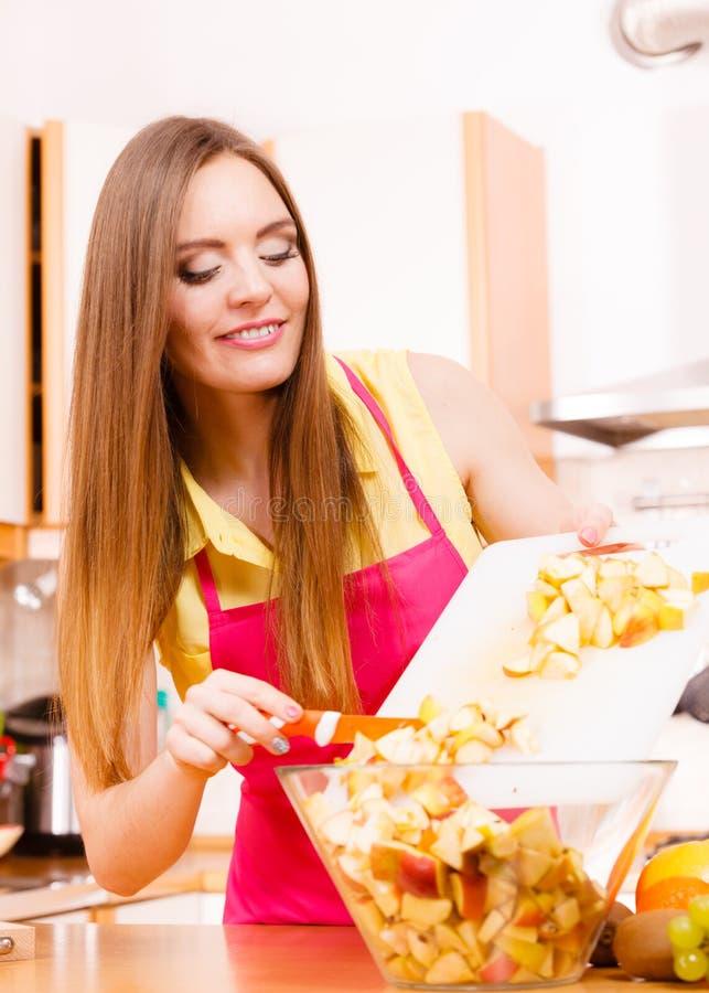 Vrouwenhuisvrouw in vruchten van de keuken de scherpe appel royalty-vrije stock foto's
