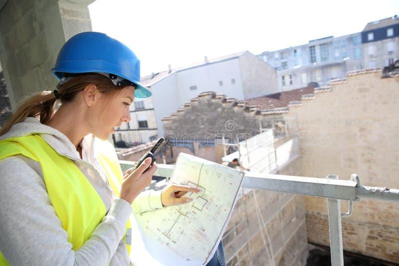 Vrouweningenieur bij bouwwerf het werken stock foto