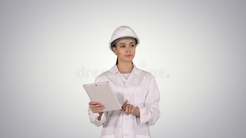 Vrouweningenieur die informatie en voorwerpen op haar tablet op gradiëntachtergrond controleren stock fotografie