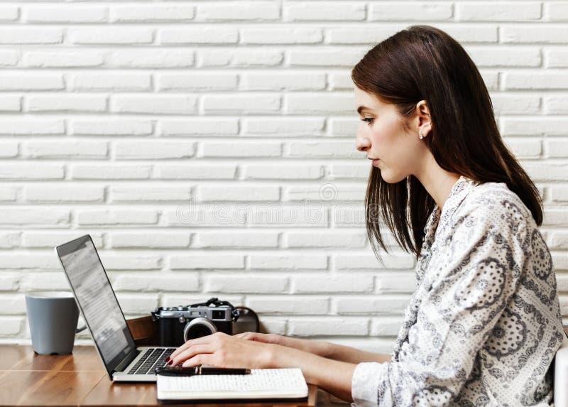 Vrouwenjournalist die computer voor het werk met behulp van stock afbeeldingen
