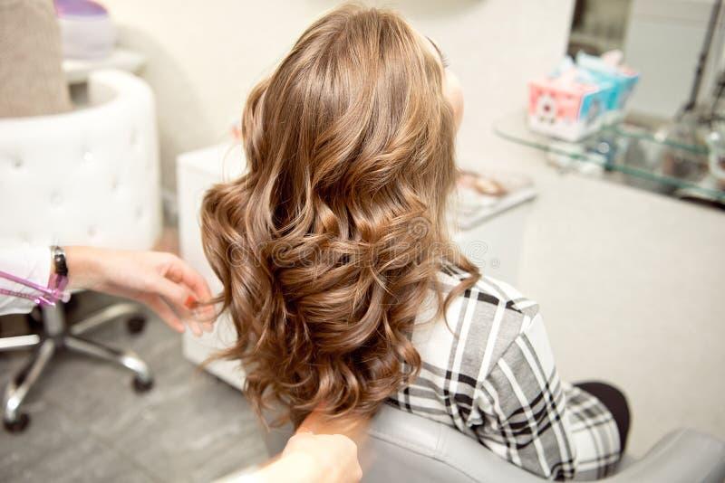 Vrouwenkapper die tot kapsel maken aan blondemeisje in schoonheidssalon royalty-vrije stock afbeelding