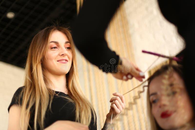Vrouwenkapper Looking bij het Krullen van Kapsel stock foto
