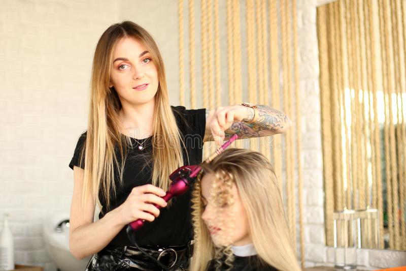 Vrouwenkapper Make Curls Hair door Ijzer Te krullen stock afbeeldingen
