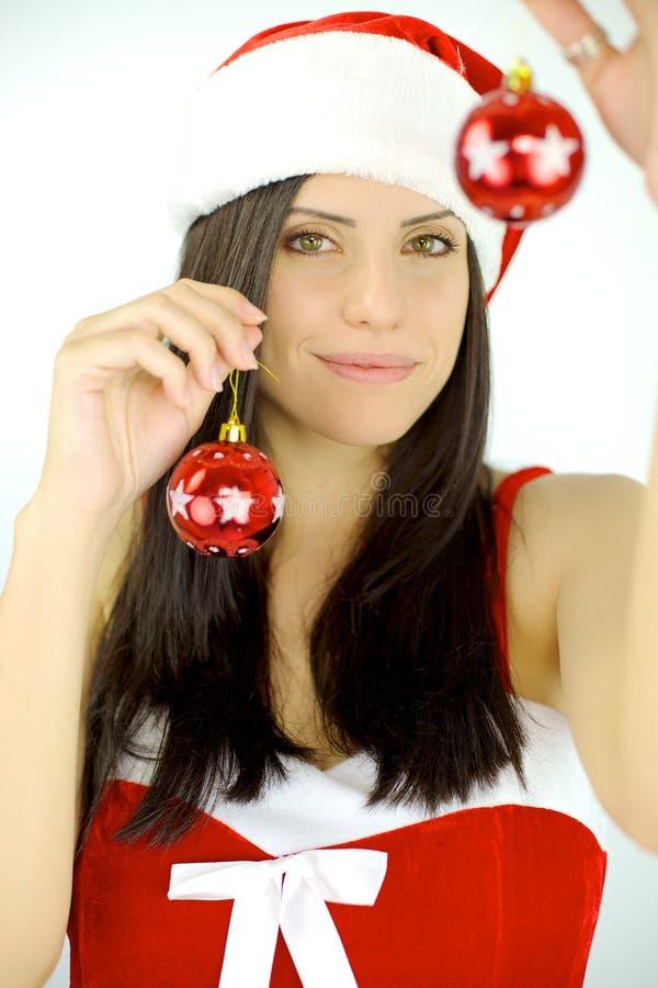 Vrouwenkerstman die Kerstmisballen houden stock fotografie