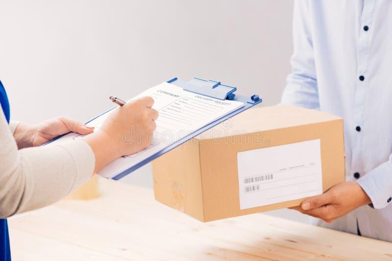 Vrouwenklant die ontvangstbewijs ondertekenen en het pakket van de leveringsmens ontvangen Zaken en logistisch concept stock fotografie