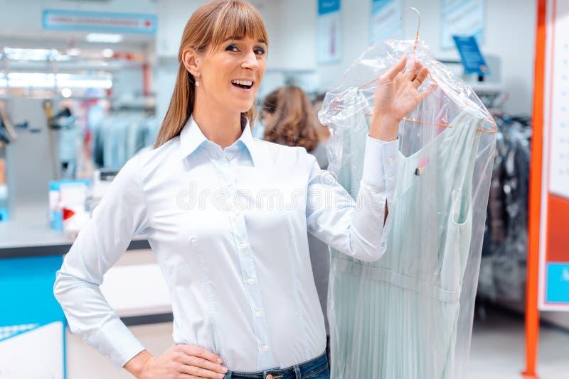 Vrouwenklant die schone kleren van het textiel schoonmaken terugkrijgen royalty-vrije stock foto's