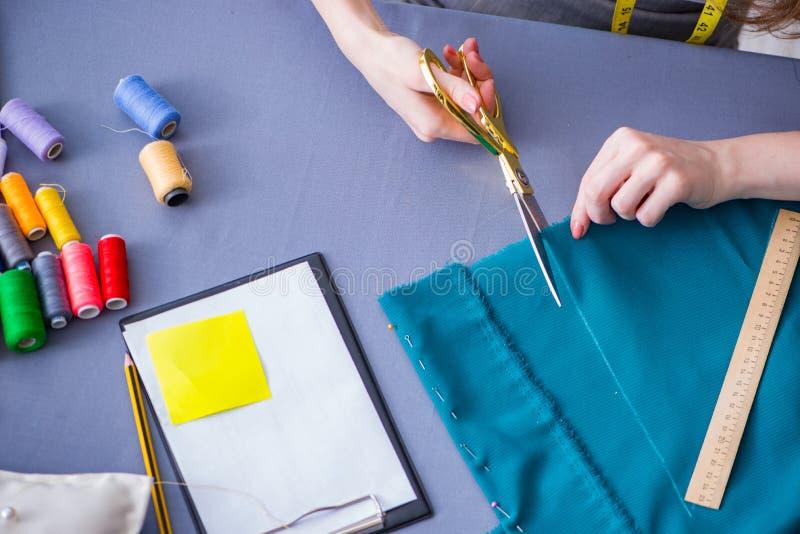 Vrouwenkleermaker die aan kleding het naaien het stikken werken metend FA stock foto
